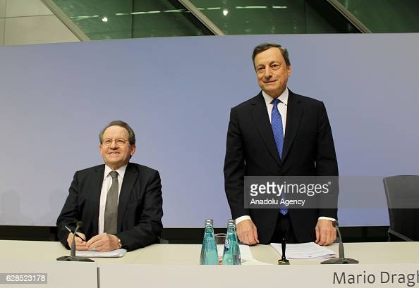 Mario Draghi president of the European Central Bank speaks as he sits beside Vitor Constancio vice president of the European Central Bank during a...