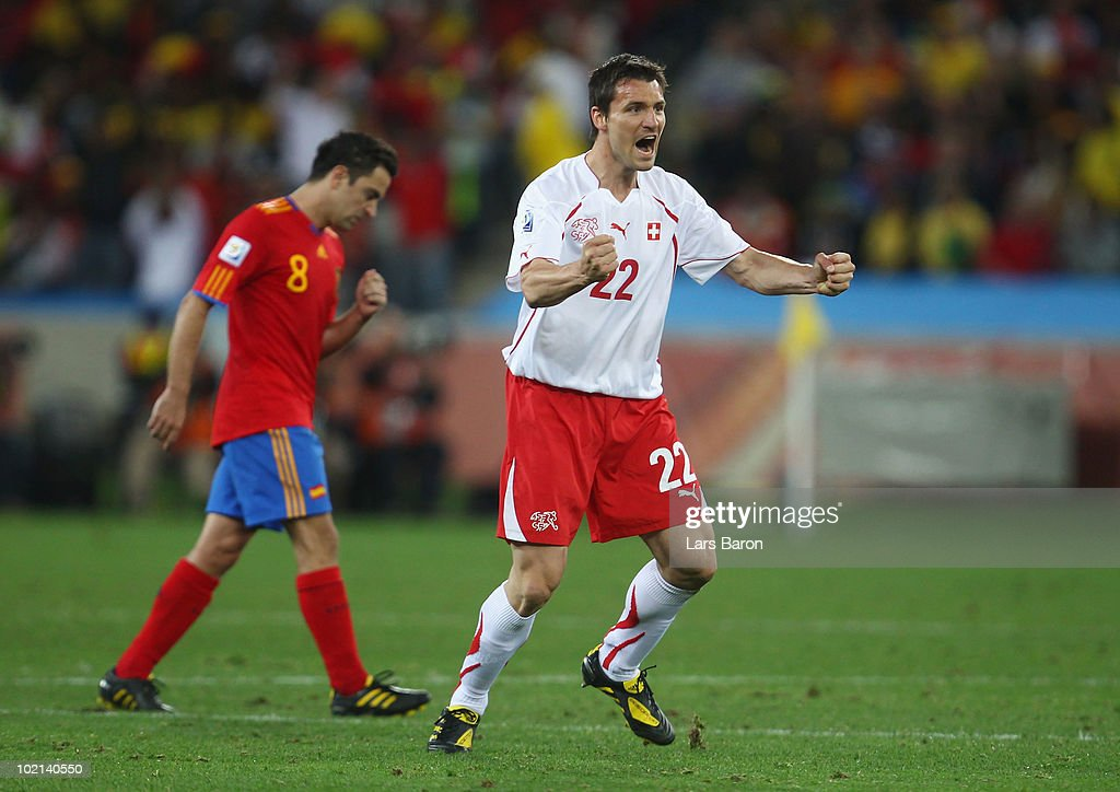 <a gi-track='captionPersonalityLinkClicked' href=/galleries/search?phrase=Mario+Eggimann&family=editorial&specificpeople=677363 ng-click='$event.stopPropagation()'>Mario Eggimann</a> of Switzerland celebrates as Xavi Hernandez of Spain walks by dejected during the 2010 FIFA World Cup South Africa Group H match between Spain and Switzerland at Durban Stadium on June 16, 2010 in Durban, South Africa.