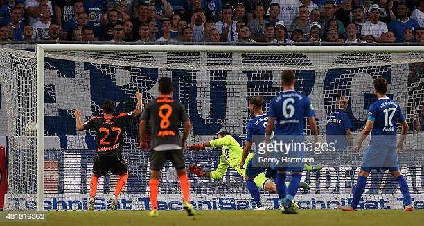 Mario Erb of Erfurt scores his team's opening goal against goalkeeper Jan Glinker of Magdeburg during the Third League match between 1 FC Magdeburg...
