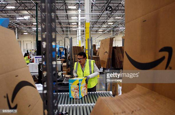 Mario Garica pushes a box of diapers along a conveyor belt at the Amazoncom Phoenix Fulfillment Center in Goodyear Arizona US on Monday Nov 16 2009...