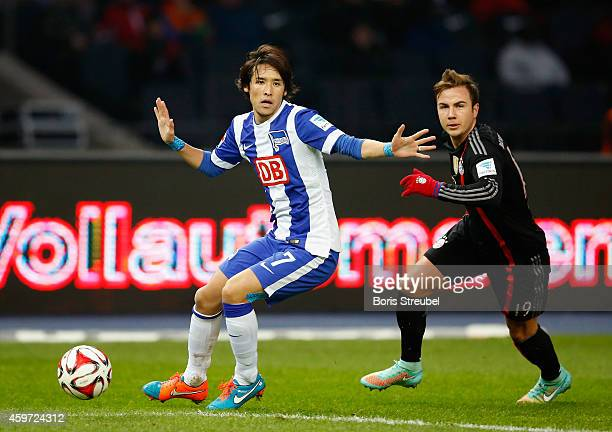 Mario Goetze of Bayern and Hajime Hosogai of Berlin battle for the ball during the Bundesliga match between Hertha BSC and FC Bayern Muenchen at...