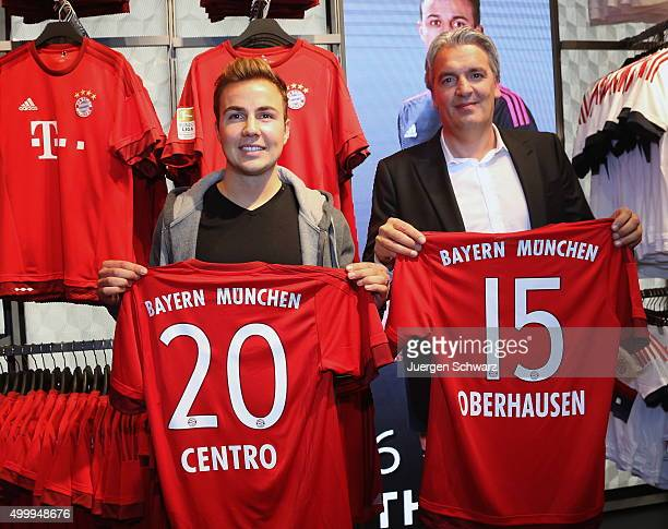 Mario Goetze of Bayern Muenchen and board member Joerg Wacker display shirts during the opening of a Bayern Munich fan shop at CentrO mall on...