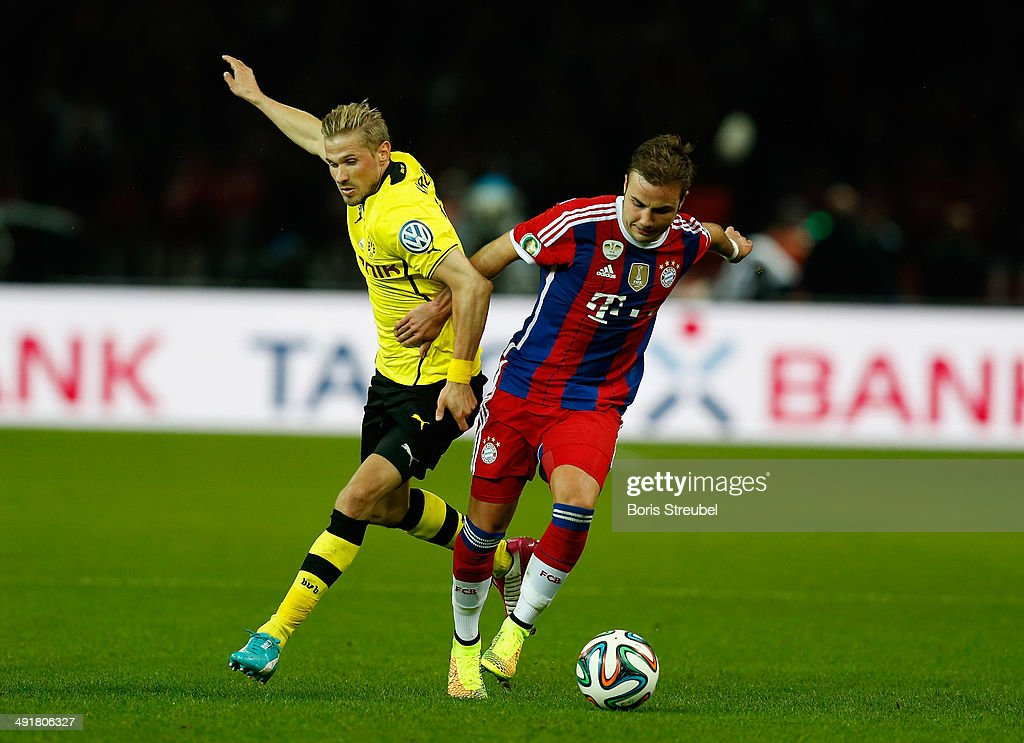 Mario Goetze (R) of Bayern Muenchen battles for the ball with Oliver Kirch of Borussia Dortmund during the DFB Cup Final match between Borussia Dortmund and Bayern Muenchen at Olympiastadion on May 17, 2014 in Berlin, Germany.