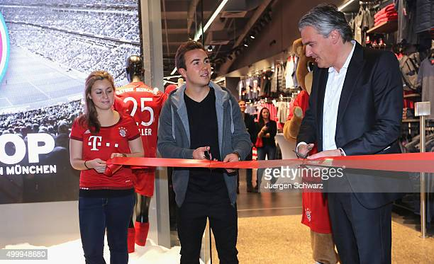 Mario Goetze of Bayern Muenchen cuts the red ribbon beside board member Joerg Wacker during the opening of a Bayern Munich fan shop at CentrO mall on...