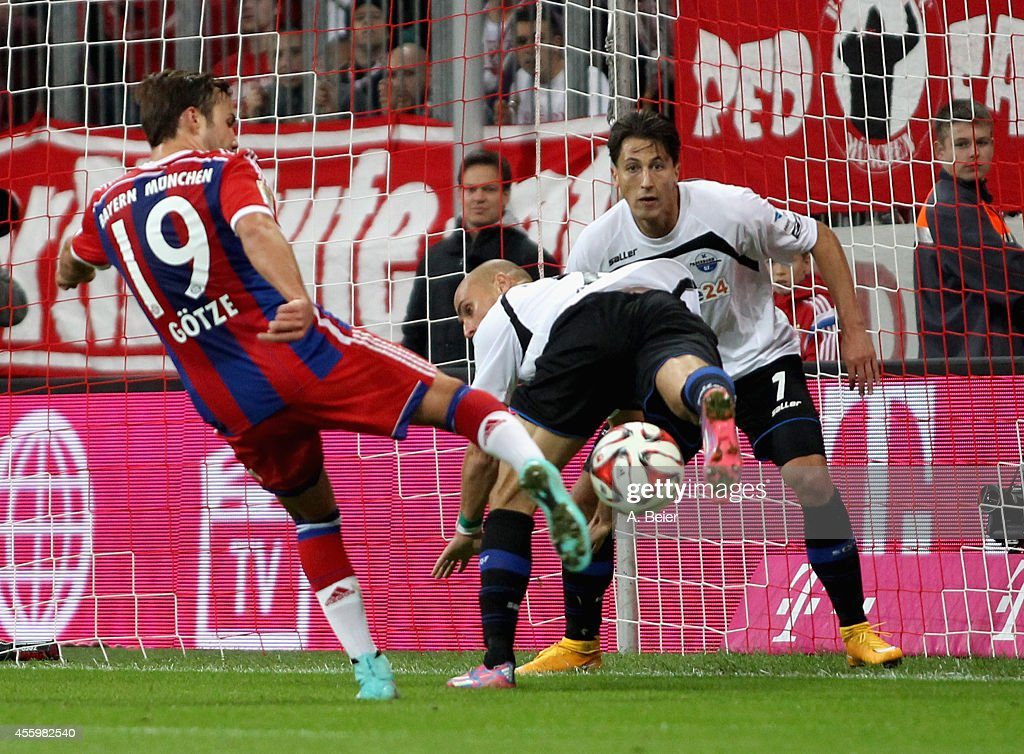 Mario Goetze of Bayern Muenchen scores a goal against Daniel Brueckner and Jens Wemmer of Paderborn during the Bundesliga match between FC Bayern...