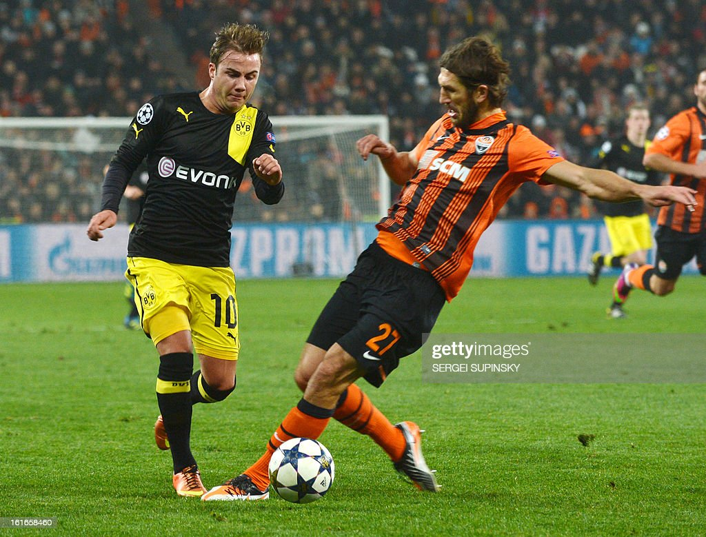 Mario Goetze (L) of Borussia Dortmund fights for a ball with Dmytro Chygrynskiy of Shakhtar Donetsk during a UEFA Champions League, Round 16, football match in Donetsk on February 13, 2013. AFP PHOTO/ SERGEI SUPINSKY