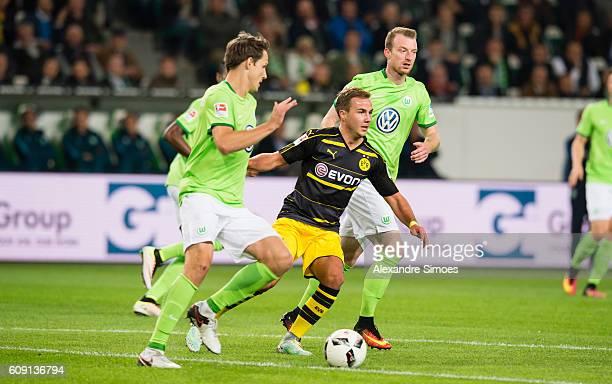 Mario Goetze of Borussia Dortmund gets challenged by Maximilian Arnold and Philipp Wollscheid of VfL Wolfsburg during the Bundesliga match between...