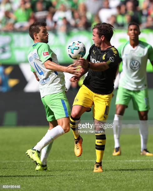 Mario Goetze of Borussia Dortmund with Ignacio Camacho of VfL Wolfsburg during the Bundesliga match between VfL Wolfsburg and Borussia Dortmund at...