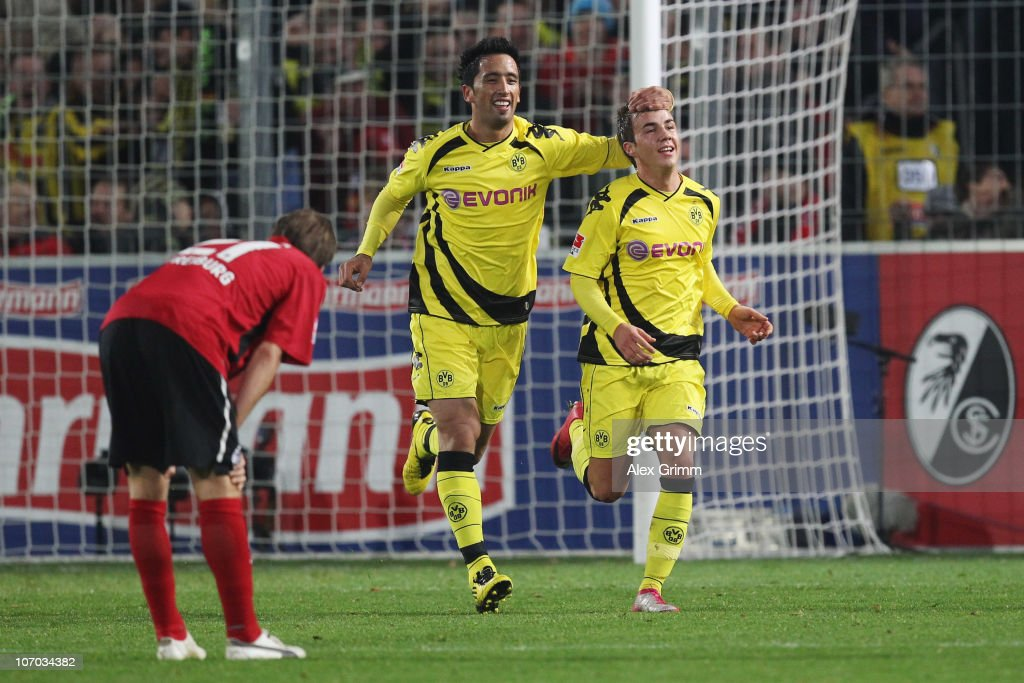 <a gi-track='captionPersonalityLinkClicked' href=/galleries/search?phrase=Mario+Goetze&family=editorial&specificpeople=4251202 ng-click='$event.stopPropagation()'>Mario Goetze</a> of Dortmund celebrates his team's second goal with team mate <a gi-track='captionPersonalityLinkClicked' href=/galleries/search?phrase=Lucas+Barrios&family=editorial&specificpeople=4142497 ng-click='$event.stopPropagation()'>Lucas Barrios</a> as Anton Putsilo (R-L) of Freiburg reacts during the Bundesliga match between SC Freiburg and Borussia Dortmund at the Badenova Stadium on November 20, 2010 in Freiburg im Breisgau, Germany.