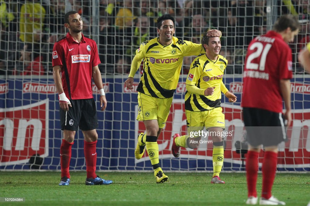 <a gi-track='captionPersonalityLinkClicked' href=/galleries/search?phrase=Mario+Goetze&family=editorial&specificpeople=4251202 ng-click='$event.stopPropagation()'>Mario Goetze</a> (2R) of Dortmund celebrates his team's second goal with team mate <a gi-track='captionPersonalityLinkClicked' href=/galleries/search?phrase=Lucas+Barrios&family=editorial&specificpeople=4142497 ng-click='$event.stopPropagation()'>Lucas Barrios</a> (2L) as <a gi-track='captionPersonalityLinkClicked' href=/galleries/search?phrase=Oemer+Toprak&family=editorial&specificpeople=5395932 ng-click='$event.stopPropagation()'>Oemer Toprak</a> (L) and Anton Putsilo (R) of Freiburg react during the Bundesliga match between SC Freiburg and Borussia Dortmund at the Badenova Stadium on November 20, 2010 in Freiburg im Breisgau, Germany.