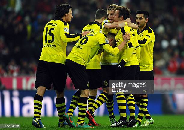 Mario Goetze of Dortmund celebrates with Marco Reus and other team mates after scoring his teams first goal during the Bundesliga match between...