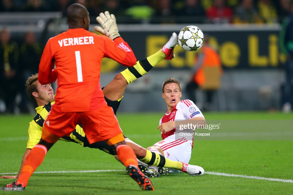 Mario Goetze of Dortmund (C) failes against Kenneth Vermeer of Amsterdam (L) and Niklas Moisander of Amsterdam (R) during the UEFA Champions League group D match between Borussia Dortmund and Ajax Amsterdam at Signal Iduna Park on September 18, 2012 in Dortmund, Germany.