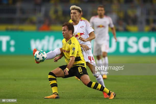 Mario Goetze of Dortmund fights for the ball with Kevin Kampl of Leipzig during the Bundesliga match between Borussia Dortmund and RB Leipzig at...