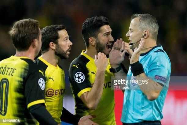 Mario Goetze of Dortmund Gonzalo Castro of Dortmund and Nuri Sahin of Dortmund speak with Referee Bjoern Kuipers during the UEFA Champions League...