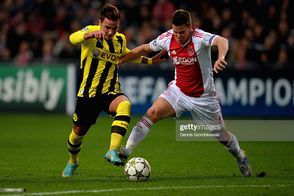 Mario Goetze of Dortmund is challenged by Niklas Moisander of Amsterdam during the UEFA Champions League Group D match between Ajax Amsterdam and Borussia Dortmund at Amsterdam Arena on November 21, 2012 in Amsterdam, Netherlands.