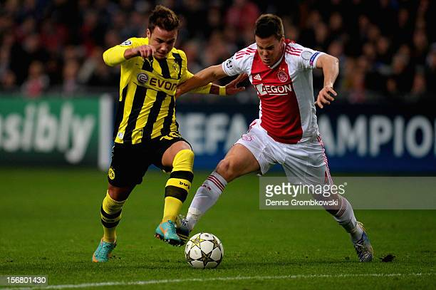 Mario Goetze of Dortmund is challenged by Niklas Moisander of Amsterdam during the UEFA Champions League Group D match between Ajax Amsterdam and...