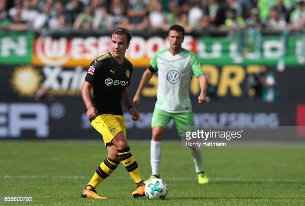 Mario Goetze of Dortmund passes the ball infront of Ignacio Camacho of Wolfsburg during the Bundesliga match between VfL Wolfsburg and Borussia...