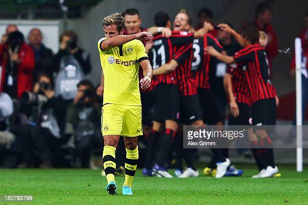 Mario Goetze of Dortmund reacts as Bamba Anderson of Frankfurt celebrates his team's third goal with team mates during the Bundesliga match between...