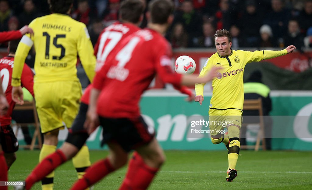 Mario Goetze (R) of Dortmund runs with the ball battle for the ball during the Bundesliga match between Bayer 04 Leverkusen and Borussia Dortmund at BayArena on February 3, 2013 in Leverkusen, Germany.