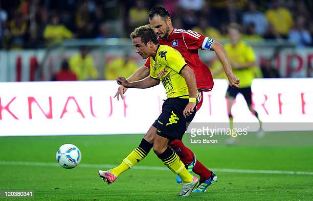 Mario Goetze of Dortmund scores his teams second goal next to Heiko Westermann of Hamburg during the Bundesliga match between Borussia Dortmund and...