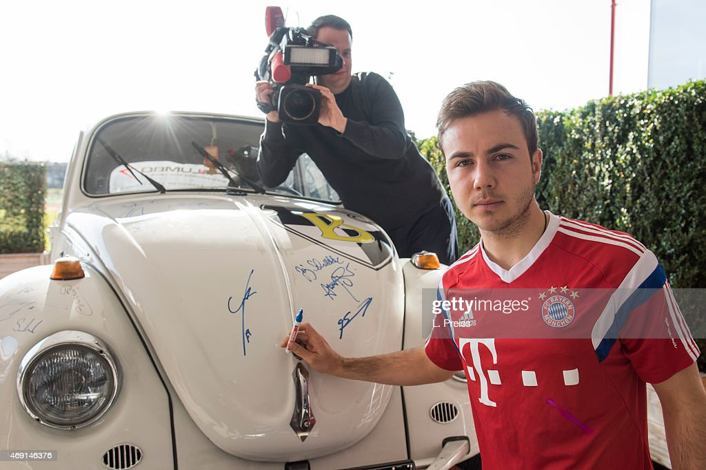 mario goetze of fc bayern muenchen signs a volkswagen beetle car for borussia neunkirchen on. Black Bedroom Furniture Sets. Home Design Ideas