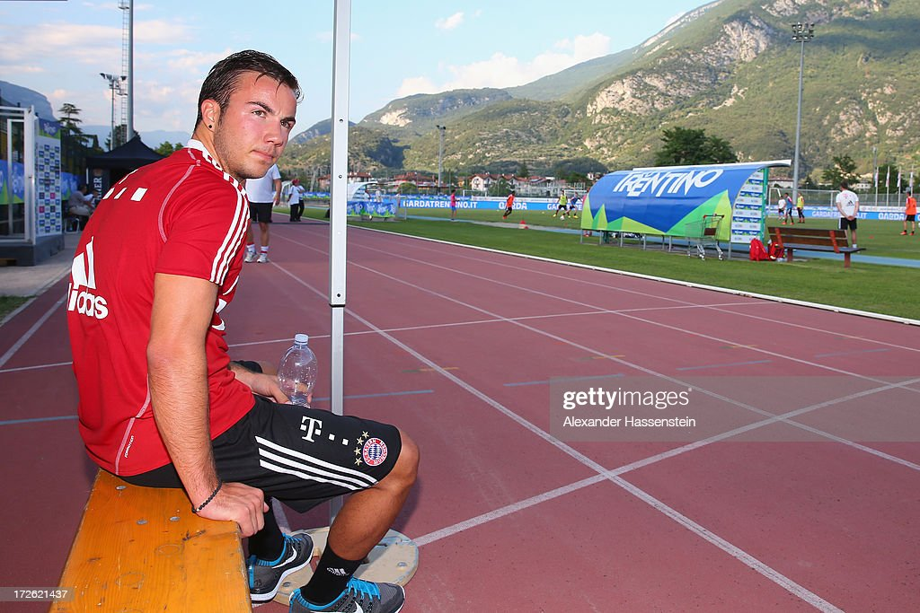 Mario Goetze of FC Bayern Muenchen watches the training session of his team mates at Campo Sportivo on July 4 2013 in Arco Italy