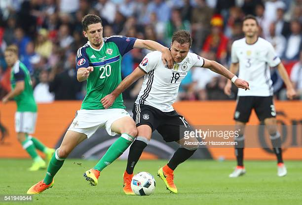 Mario Goetze of Germany and Craig Cathcart of Northern Ireland compete for the ball during the UEFA EURO 2016 Group C match between Northern Ireland...
