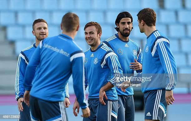 Mario Goetze of Germany and Sami Khedira of Germany joke with Toni Kross of Germany and Thomas Mueller of Germany during a training session ahead of...