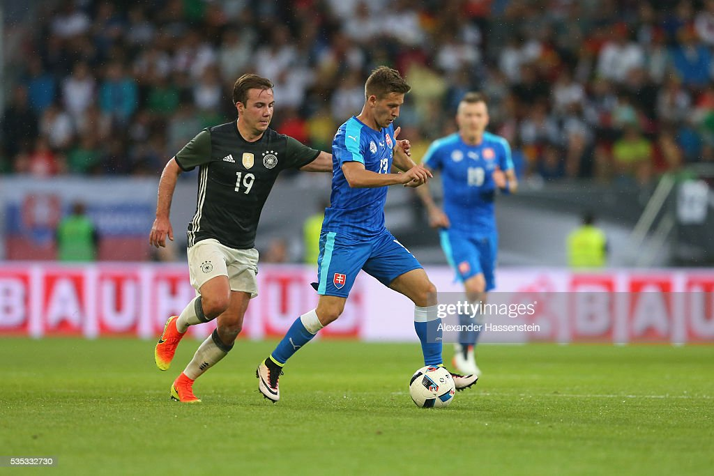 <a gi-track='captionPersonalityLinkClicked' href=/galleries/search?phrase=Mario+Goetze&family=editorial&specificpeople=4251202 ng-click='$event.stopPropagation()'>Mario Goetze</a> (L) of Germany battles for the ball with Patrick Hrosovsky of Slovakia during the international friendly match between Germany and Slovakia at WWK-Arena on May 29, 2016 in Augsburg, Germany.
