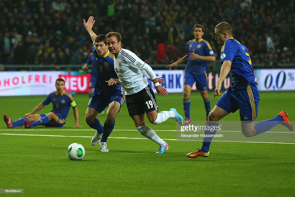 Mario Goetze (C) of Germany battles for the ball with Viktor Dmitrenko (L) of Kazakhstan and his team mate Mark Gurman (R) during the FIFA 2014 World Cup qualifier group C match between Kazakhstan and Germany at Astana Arena on March 22, 2013 in Astana, Kazakhstan.