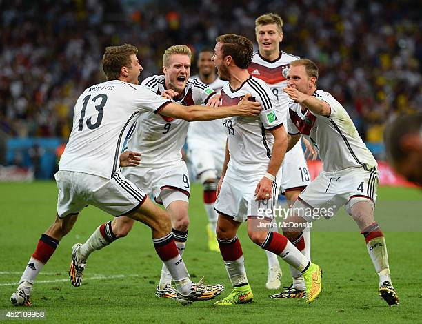Mario Goetze of Germany celebrates scoring his team's first goal in extra time with teammates Thomas Mueller Andre Schuerrle Toni Kroos and Benedikt...