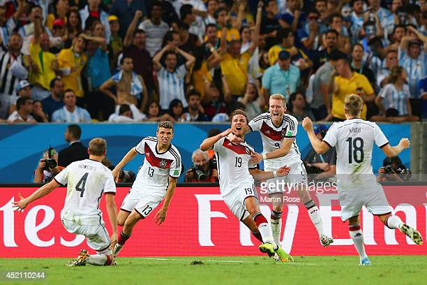 Mario Goetze of Germany celebrates scoring his team's first goal in extra time with Benedikt Hoewedes Thomas Mueller Andre Schuerrle and Toni Kroos...