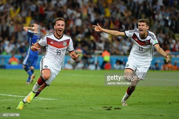 Mario Goetze of Germany celebrates scoring his team's first goal with Thomas Mueller during the 2014 FIFA World Cup Brazil Final match between...