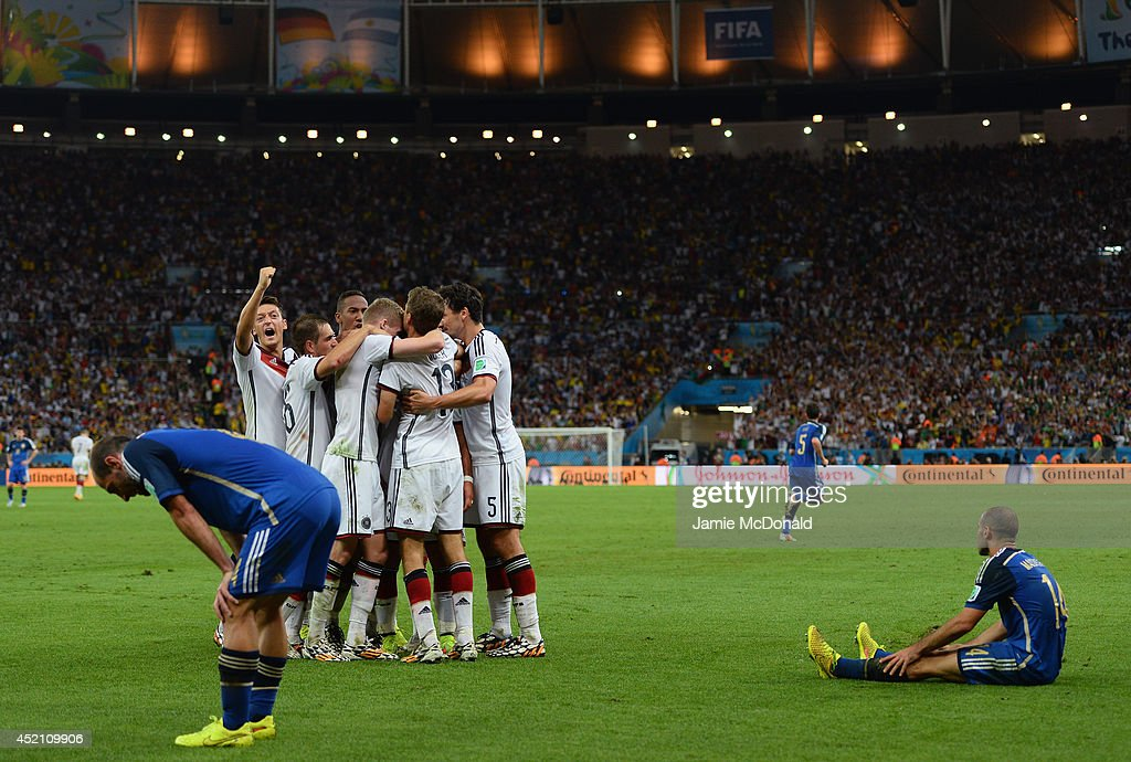 <a gi-track='captionPersonalityLinkClicked' href=/galleries/search?phrase=Mario+Goetze&family=editorial&specificpeople=4251202 ng-click='$event.stopPropagation()'>Mario Goetze</a> of Germany celebrates scoring his team's first goal with teammates as a dejected Pablo Zabaleta (L) and <a gi-track='captionPersonalityLinkClicked' href=/galleries/search?phrase=Javier+Mascherano&family=editorial&specificpeople=490876 ng-click='$event.stopPropagation()'>Javier Mascherano</a> of Argentina look on during the 2014 FIFA World Cup Brazil Final match between Germany and Argentina at Maracana on July 13, 2014 in Rio de Janeiro, Brazil.