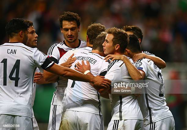 Mario Goetze of Germany celebrates with team mates after scoring his teams third goal during the EURO 2016 Qualifier Group D match between Germany...