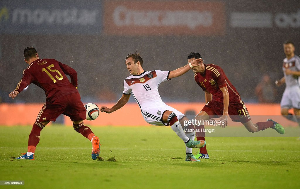 Mario Goetze of Germany falls to the ground after battling for the ball with Sergio Ramos and Bruno Soriano of Spain during the International...