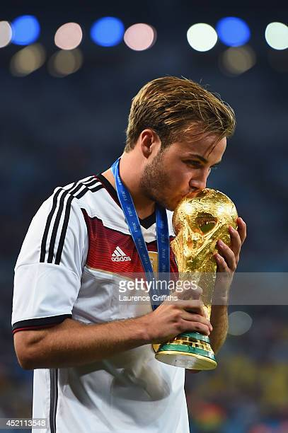 Mario Goetze of Germany kisses the World Cup trophy after defeating Argentina 10 in extra time during the 2014 FIFA World Cup Brazil Final match...