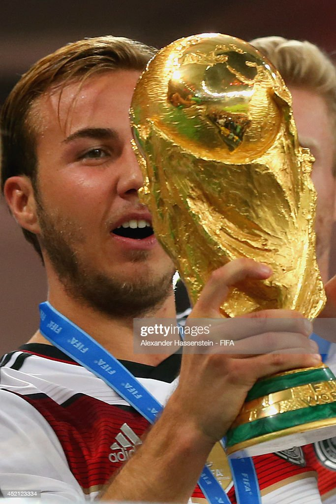 Mario Goetze of Germany lifts the World Cup trophy to celebrate with his teammates during the award ceremony after the 2014 FIFA World Cup Brazil Final match between Germany and Argentina at Maracana on July 13, 2014 in Rio de Janeiro, Brazil.