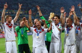 Mario Goetze of Germany raises the World Cup trophy with teammates Per Mertesacker RonRobert Zieler Shkodran Mustafi Roman Weidenfeller Mats Hummels...