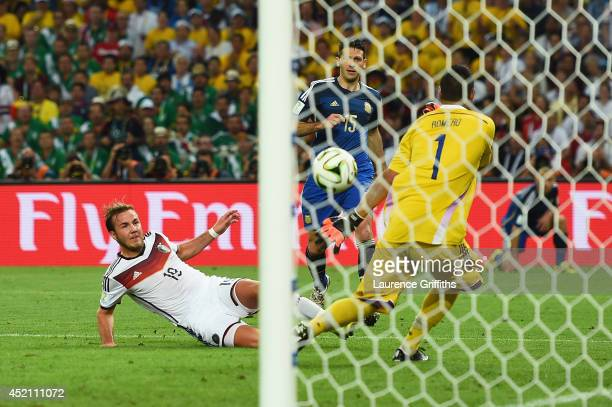 Mario Goetze of Germany scores his team's first goal past Sergio Romero of Argentina in extra time during the 2014 FIFA World Cup Brazil Final match...