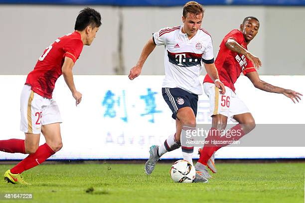 Mario Goetze of Muenchen battles for the ball with Zou Zheng of Guangzhou and his team mate during the international friendly match between FC...