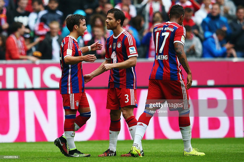 Mario Goetze of Muenchen celebrates his team's first goal with team mates Xabi Alonso and Jerome Boateng during the Bundesliga match between FC...