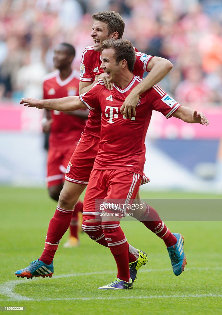 Mario Goetze (front) of Muenchen celebrates with team mate Thomas Mueller after scoring his team's 3rd goal during the Bundesliga match between FC Bayern Muenchen and Hertha BSC Berlin at Allianz Arena at Allianz Arena on October 26, 2013 in Munich, Germany.