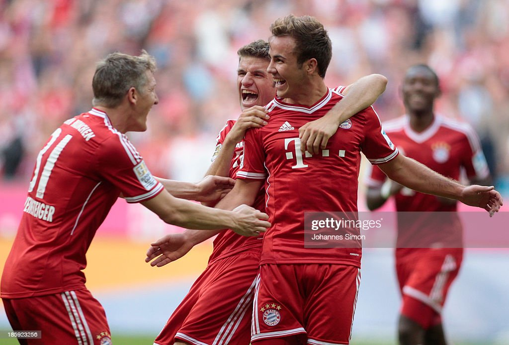 Mario Goetze (R) of Muenchen celebrates with team mates Bastian Schweinsteiger (L) and Thomas Mueller after scoring his team's 3rd goal during the Bundesliga match between FC Bayern Muenchen and Hertha BSC Berlin at Allianz Arena at Allianz Arena on October 26, 2013 in Munich, Germany.
