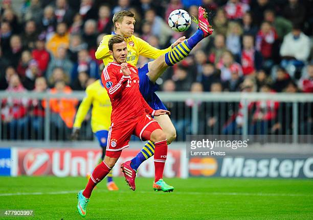 Mario Goetze of Muenchen challenges Per Mertesacker of Arsenal during the UEFA Champions League Round of 16 second leg match between FC Bayern...