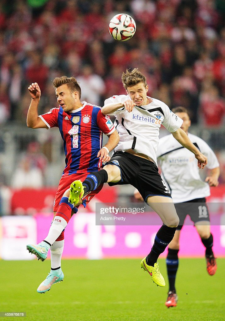 Mario Goetze of Muenchen is challenged by Patrick Ziegler of Paderborn during the Bundesliga match between FC Bayern Muenchen and SC Paderborn 07 at...