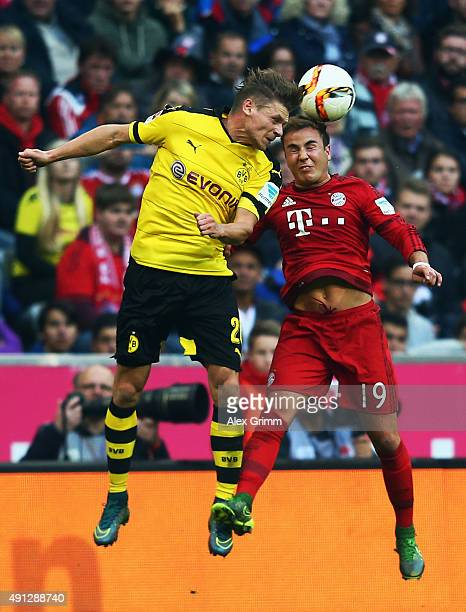 Mario Goetze of Muenchen jumps for a header with Lukas Piszczek of Dortmund during the Bundesliga match between FC Bayern Muenchen and Borussia...