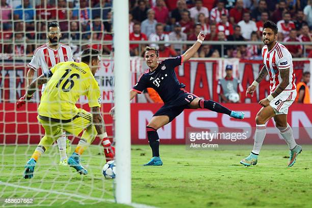 Mario Goetze of Muenchen scores his team's third goal against goalkeeper Roberto and Manuel da Costa of Olympiacos during the UEFA Champions League...