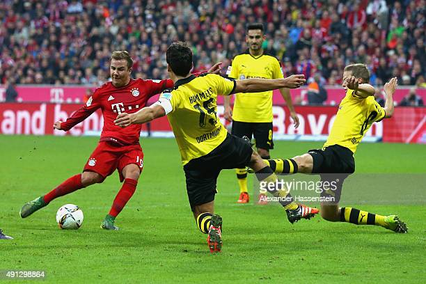 Mario Goetze of Muenchen scores the 5th team goal against Mats Hummels of Dortmund and his team mate Sven Bender during the Bundesliga match between...