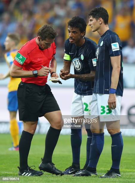 Mario Gomez and Luiz Gustavo of Wolfsburg discuss with referee Tobias Stieler after a yellow card for Gomez during the Bundesliga Playoff leg 2 match...